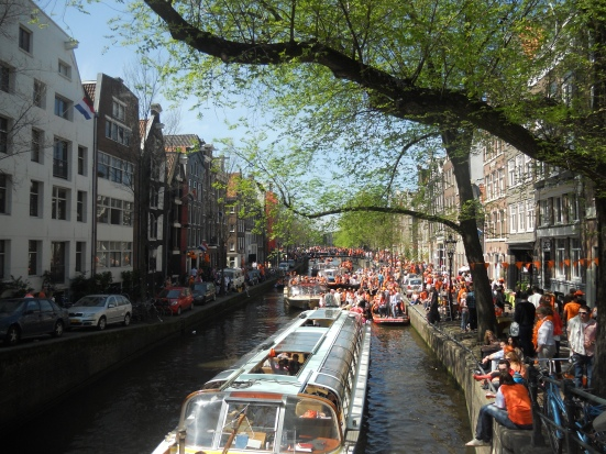 Party goers along the canals - Queen's Day, Amsterdam